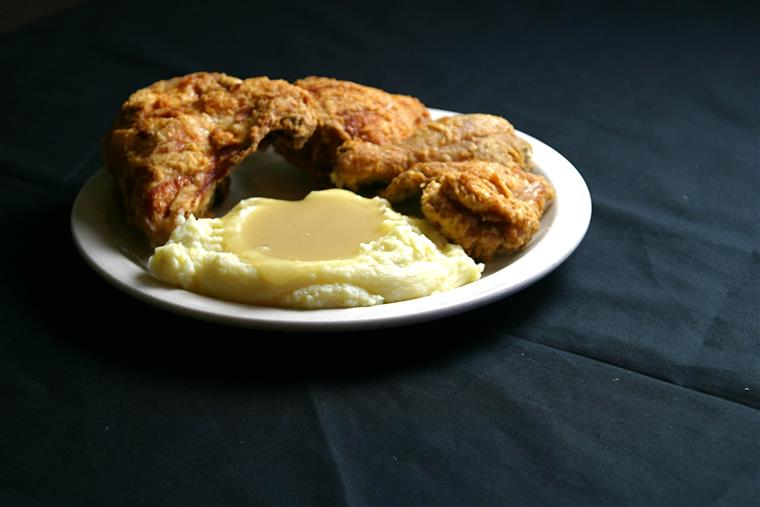 a piece of fried chicken with mashed potatoes and gravy on a white plate