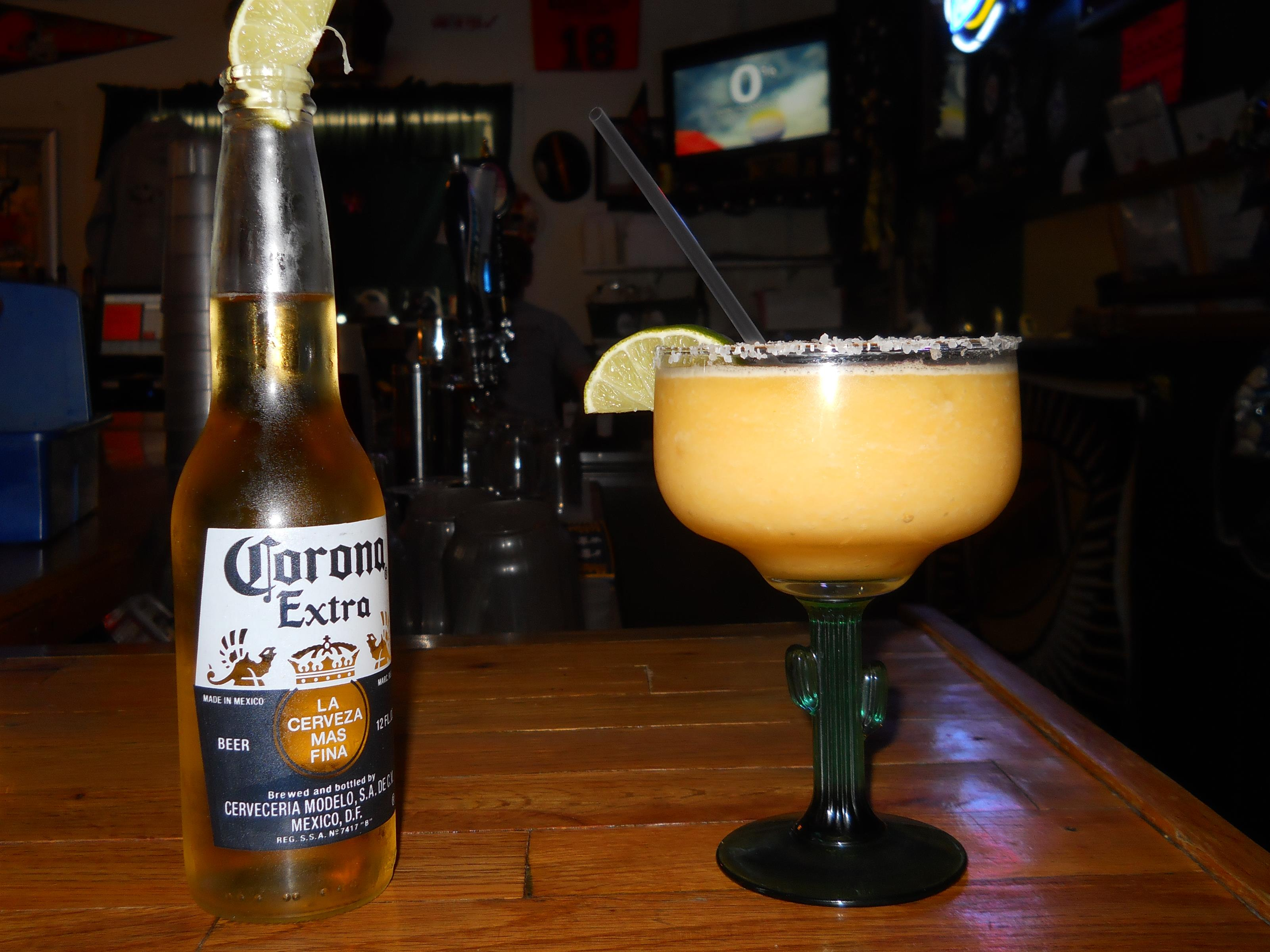 mixed drink with a corona bottle on the bar counter