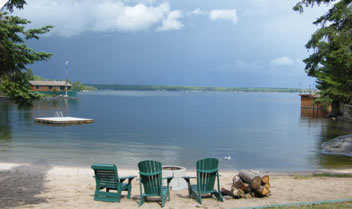 three chairs and a pile of wood with a fire pit over looking the lake on a cloudy day