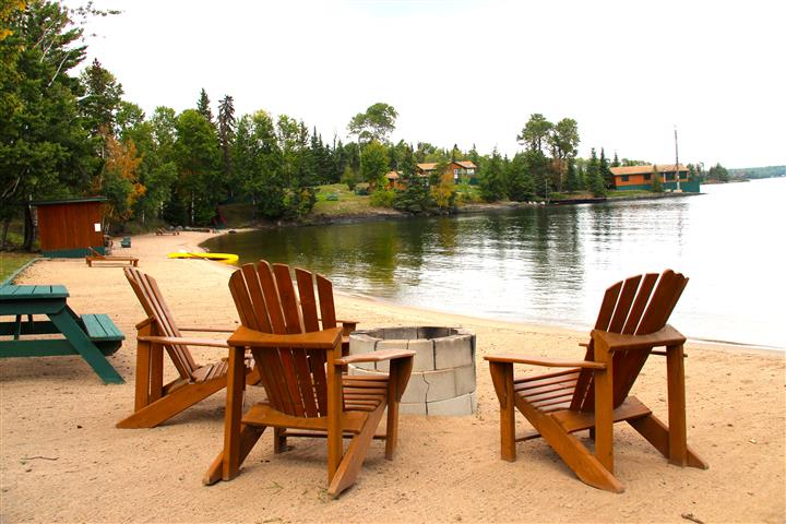 three chairs on the shore in the sand over looking the lake with a fire pit in front of the chairs