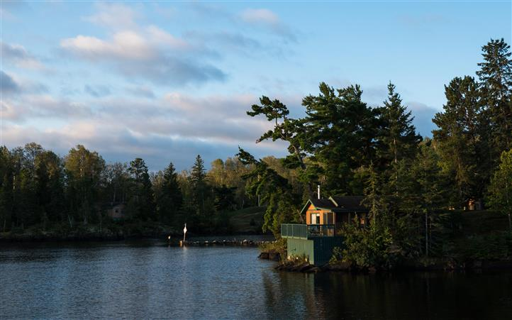 view of the lake with a cabin and some trees