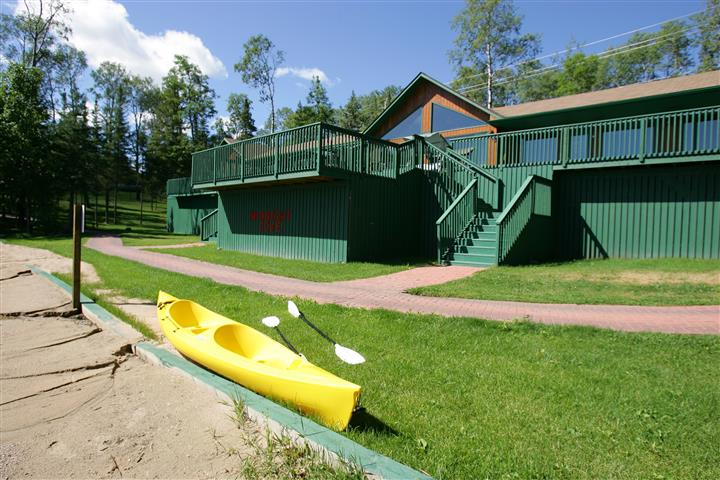 outside view of the lodge with a kayak in front of some stairs and the sand