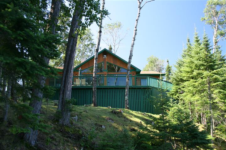 Cabin with a balcony and some trees around it during the day time