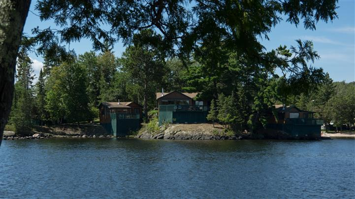 view of a cabin on the calm lake with trees around it