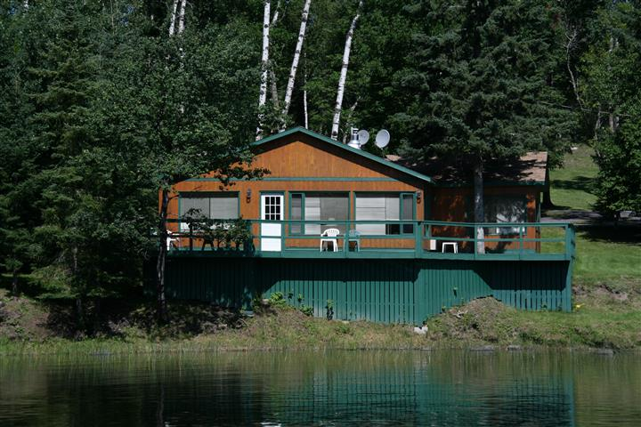 outside view of a cabin with a balcony surrounded by trees