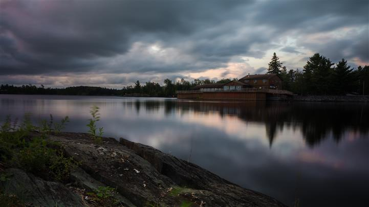 shore view of the lake and totem lodge during a cloudy day