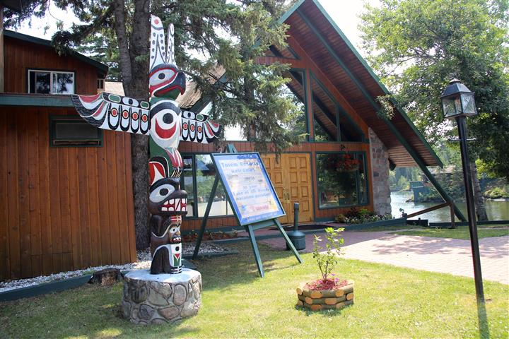 front entrance view to Totem Lodge resort and a totem pole