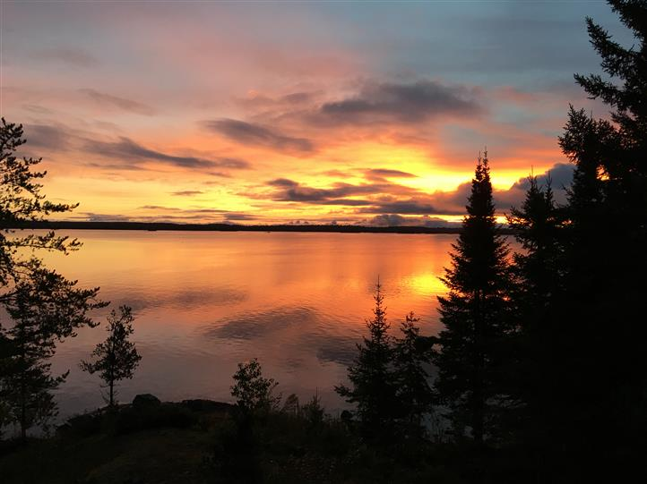 sunrise view of the lake with trees and clouds