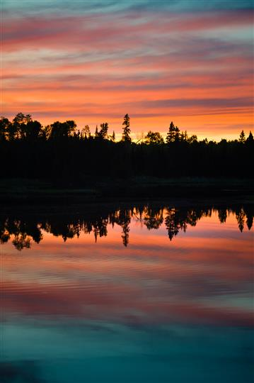 sunset view of a calm lake with trees