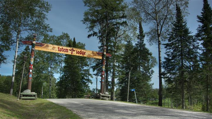 Picture of a entrance to Totem Lodge with a sign between two trees saying Totem Lodge