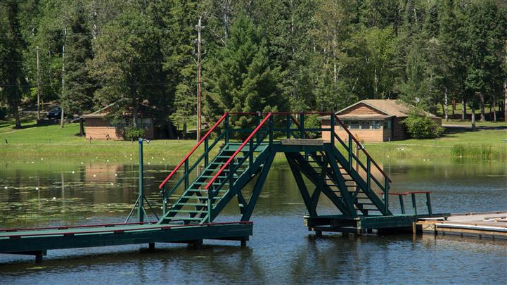 bridge with stairs on a dock going between the lake and resort