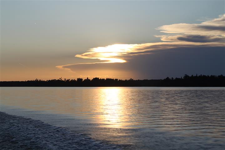 view of the lake from the shore with the sun hidding behind clouds