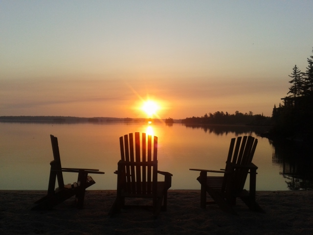 sunset view over the lake with three chairs on the beach