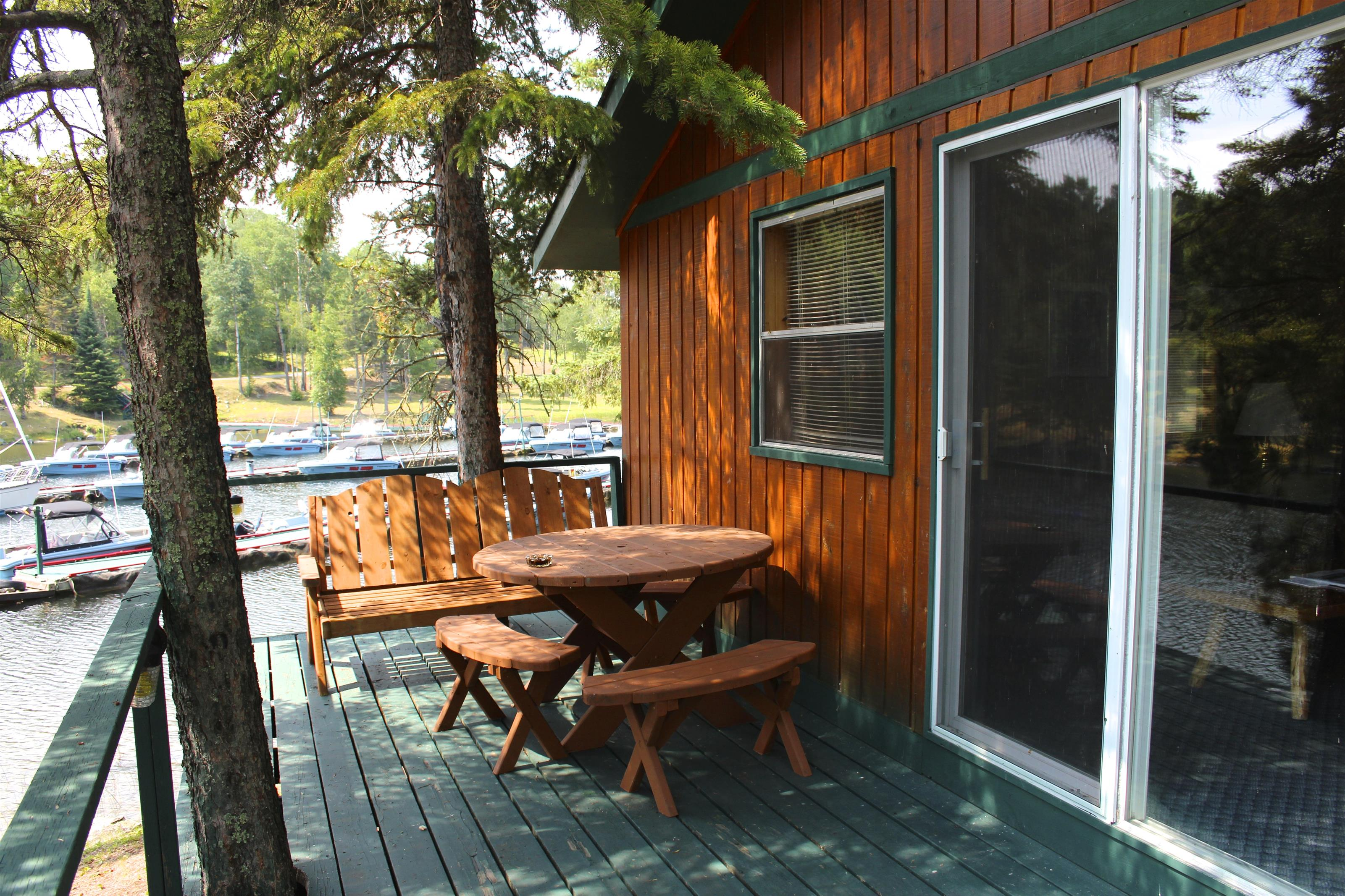outside view of a cabin from the cabins deck with a table and some benches