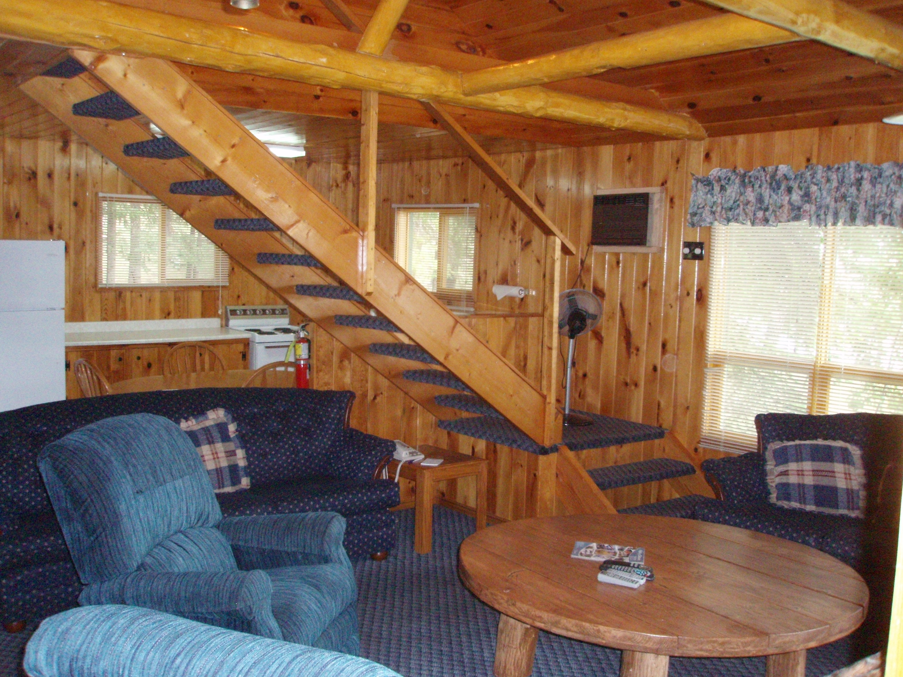 inside view of one of the cabins main areas with a couch, chair, table, stairs leading up to the next floor