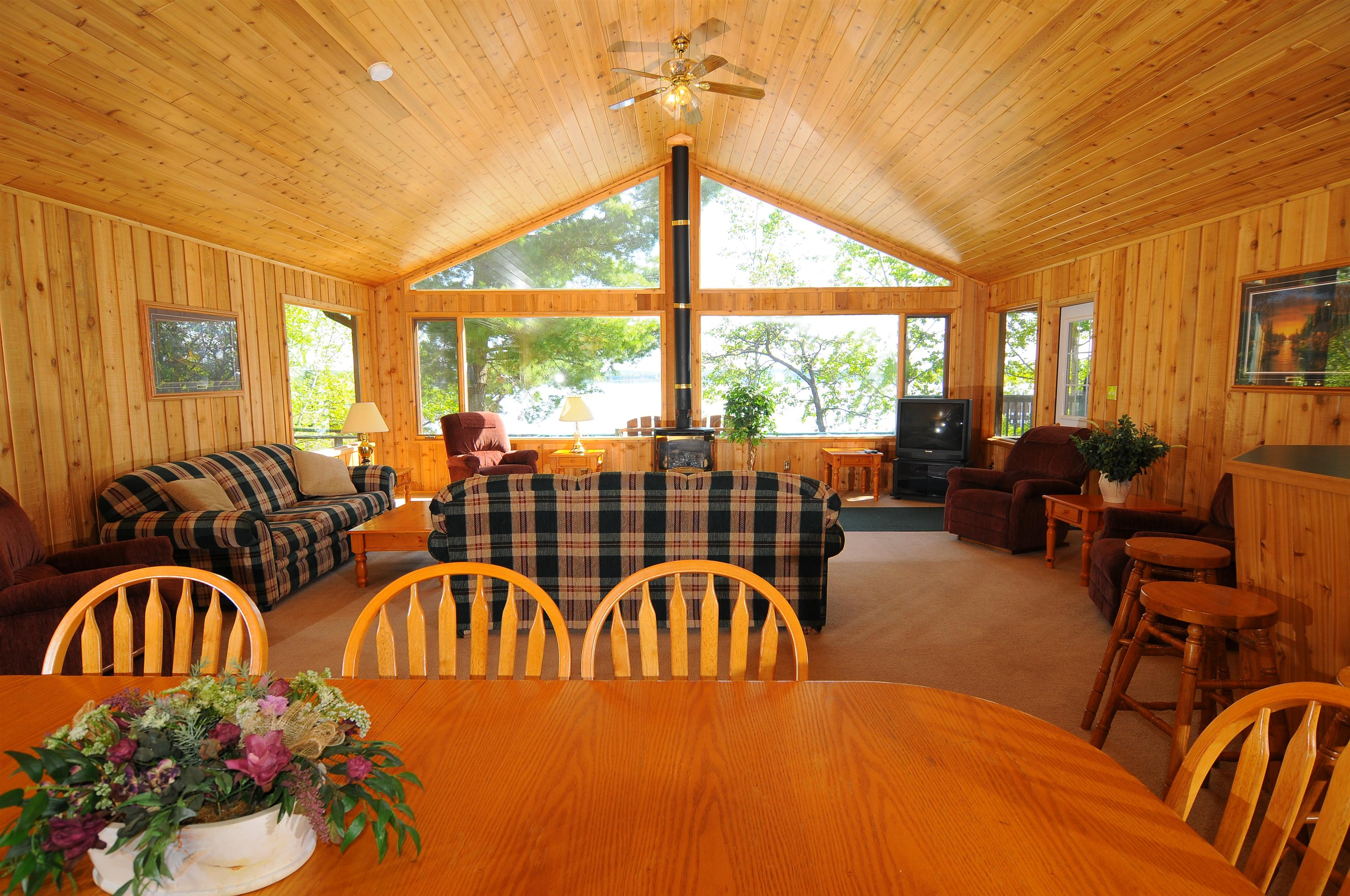 picture of a room in the cabins with a few couches, a table with chairs and a giant window looking out to the lake