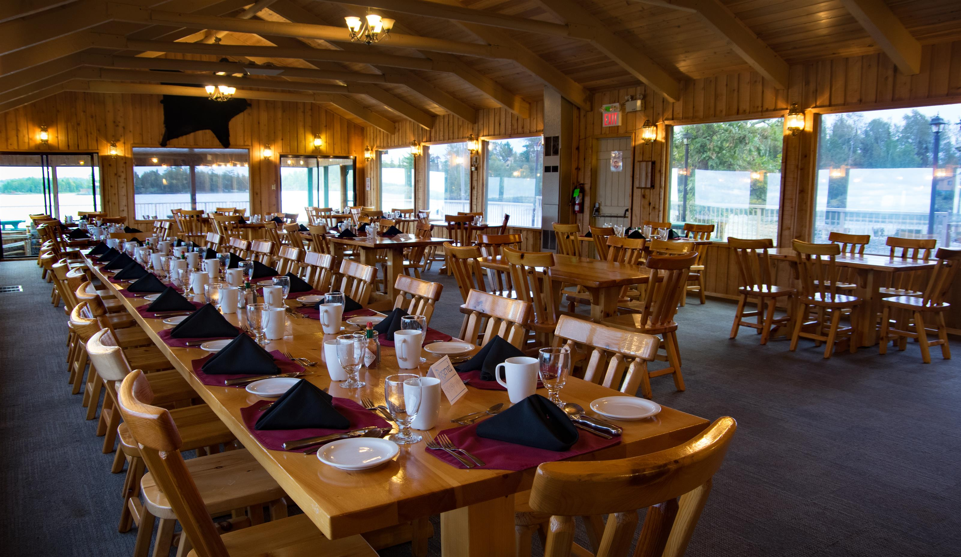 picture of a long dining table and some other tables set up for an event inside the lodge