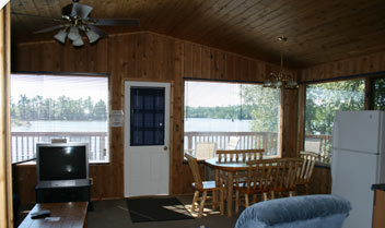 inside of a cabin with a kitchen table and chairs looking out towards the water