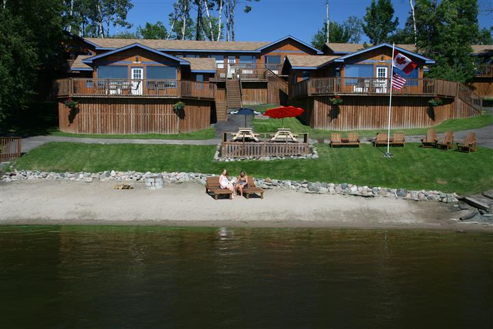 outside view of one of the cabins with guest outside sitting in chairs by the water