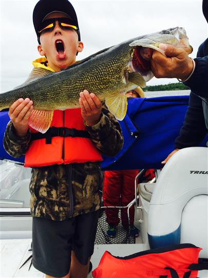 a kid holding a fish he caught