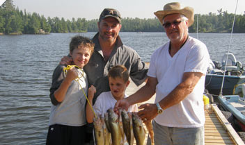 two men and two kids holding fish on a boat
