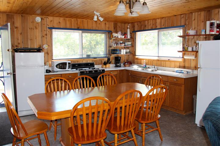 a full kitchen with a table and chairs