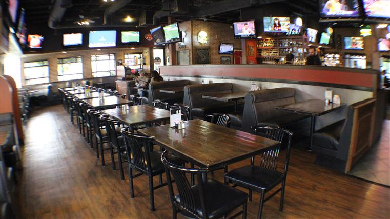 Empty Dining Room of tables and booths with Televisions throughout