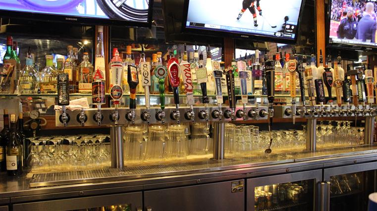 Back of bar showing beer taps, liquor bottles on shelves and television sets on walls.