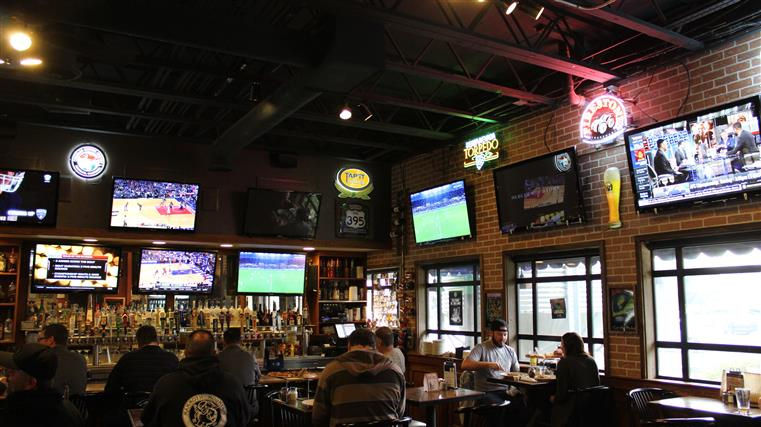 Dining room and bar area wtih tvs on walls and patrons in seats eating and drinking