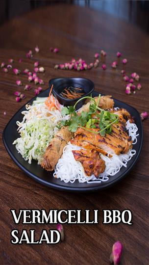 Vermicelli BBQ salad consisiting of white noodles topped with BBQ chicken, egg rolls, vegetables and dipping sauce