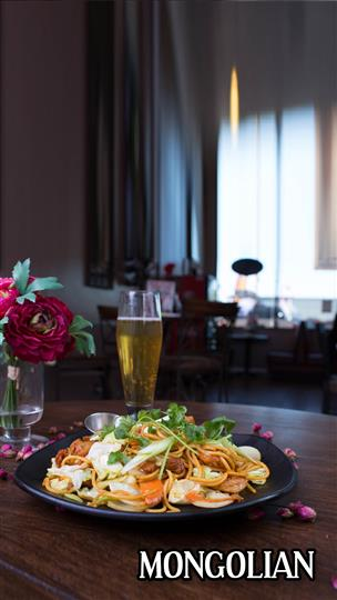 Mongolian noodles with vegetables and a beer next to a flower centerpiece