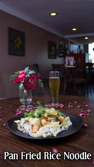Panfried rice noodle with a glass of beer next to a flower centerpiece