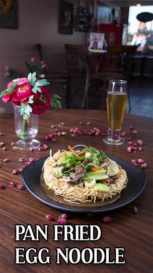 Pan fried egg noodles with a glass of beer next to a flower centerpiece