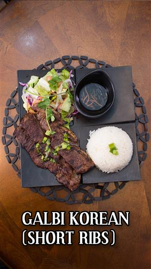 Galbi Korean Short Ribs with a ball of white rice, side slad and brown dipping sauce