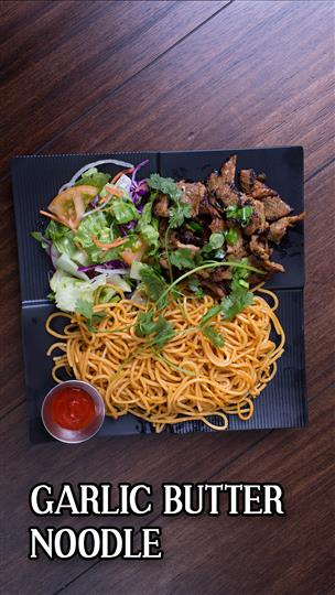 Garlic buttter noodles with grilled meat and a side slad