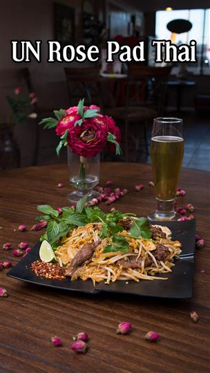 Rose pad Thai next to a glass of beer
