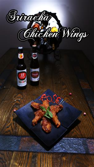"sriracha chicken wings with ""Rose"" written in sriracha on the plate and two bottles of sauce in the background"