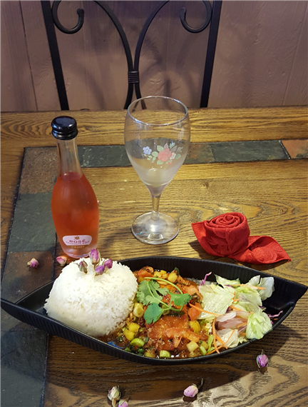 entree in a bowl with white rice and a bottle of rose on the side all displayed on a wooden table