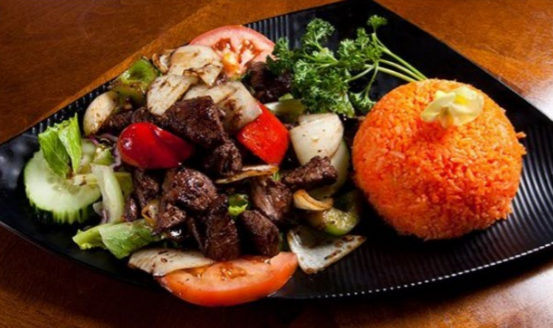 Grilled beef over vegetables next to orange rice plated with sliced tomatoes