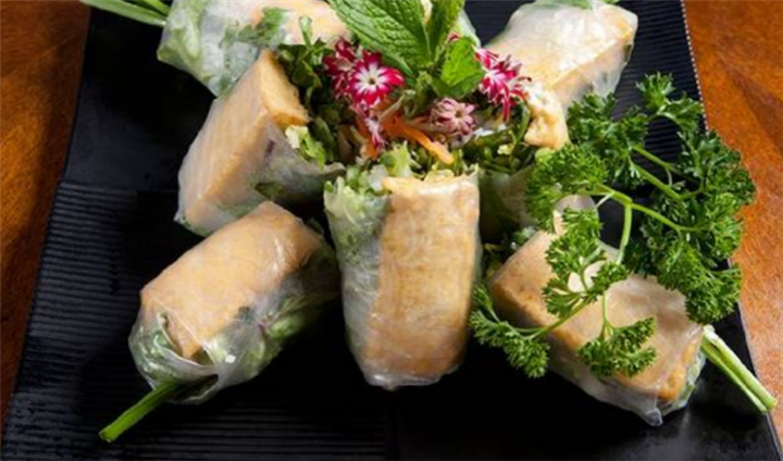 Tofu rolls plated with edible flower garnish
