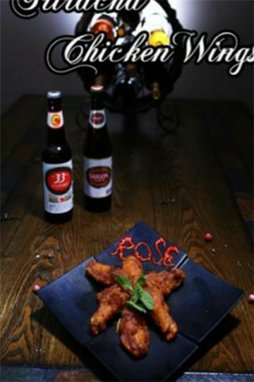 "Sriracha chicken wings with ""Rose"" written in sriracha and two bottles of sauce in the background"