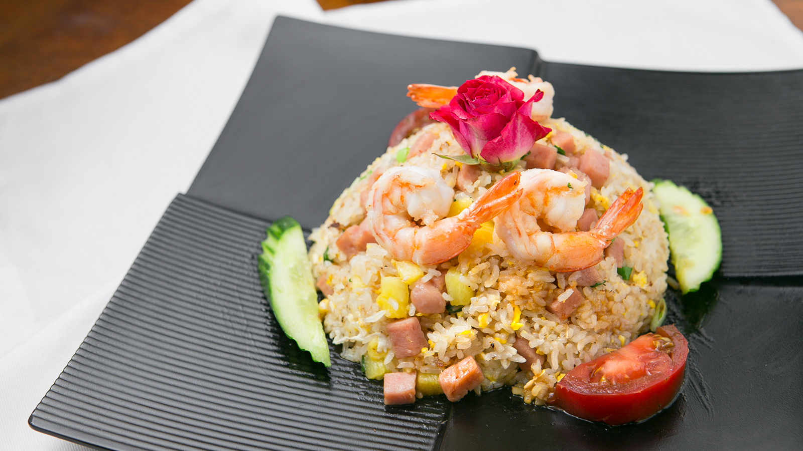 Shrimp plated over fried rice with vegetables topped with a small rose