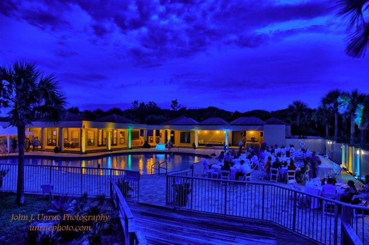 People dining by pool under blue evening sky