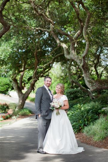 couple posing under trees on their wedding day