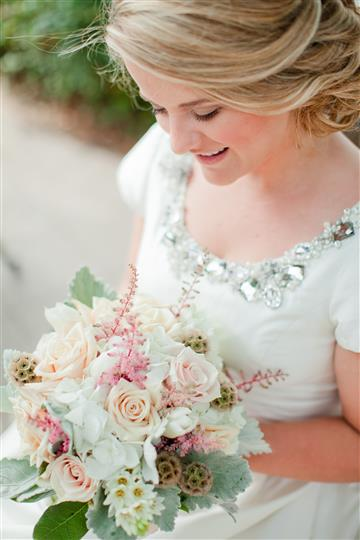 bride looking down at her boquet of flowers