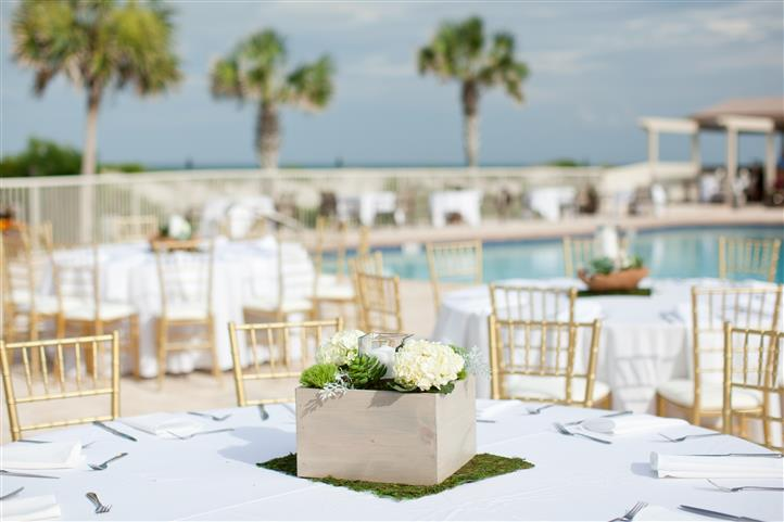 wedding set up poolside, white table clothes and gold chairs.