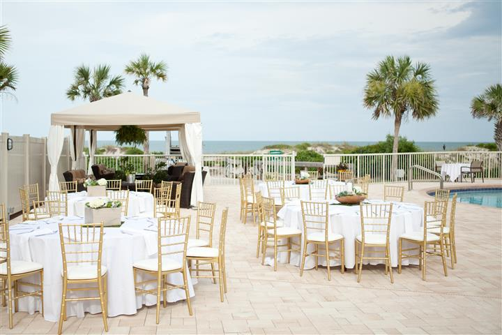 15outdoor wedding set up with white tables and gold chairs