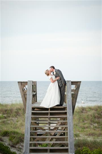 couple kissing on the boardwalk leading to the beach