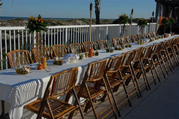outdoor wedding set up with white table clothes and wooden chairs with orange and green table accents
