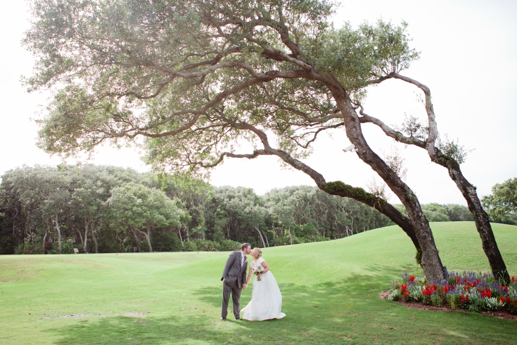 Couple in wedding attire kissing under a tree on their wedding day